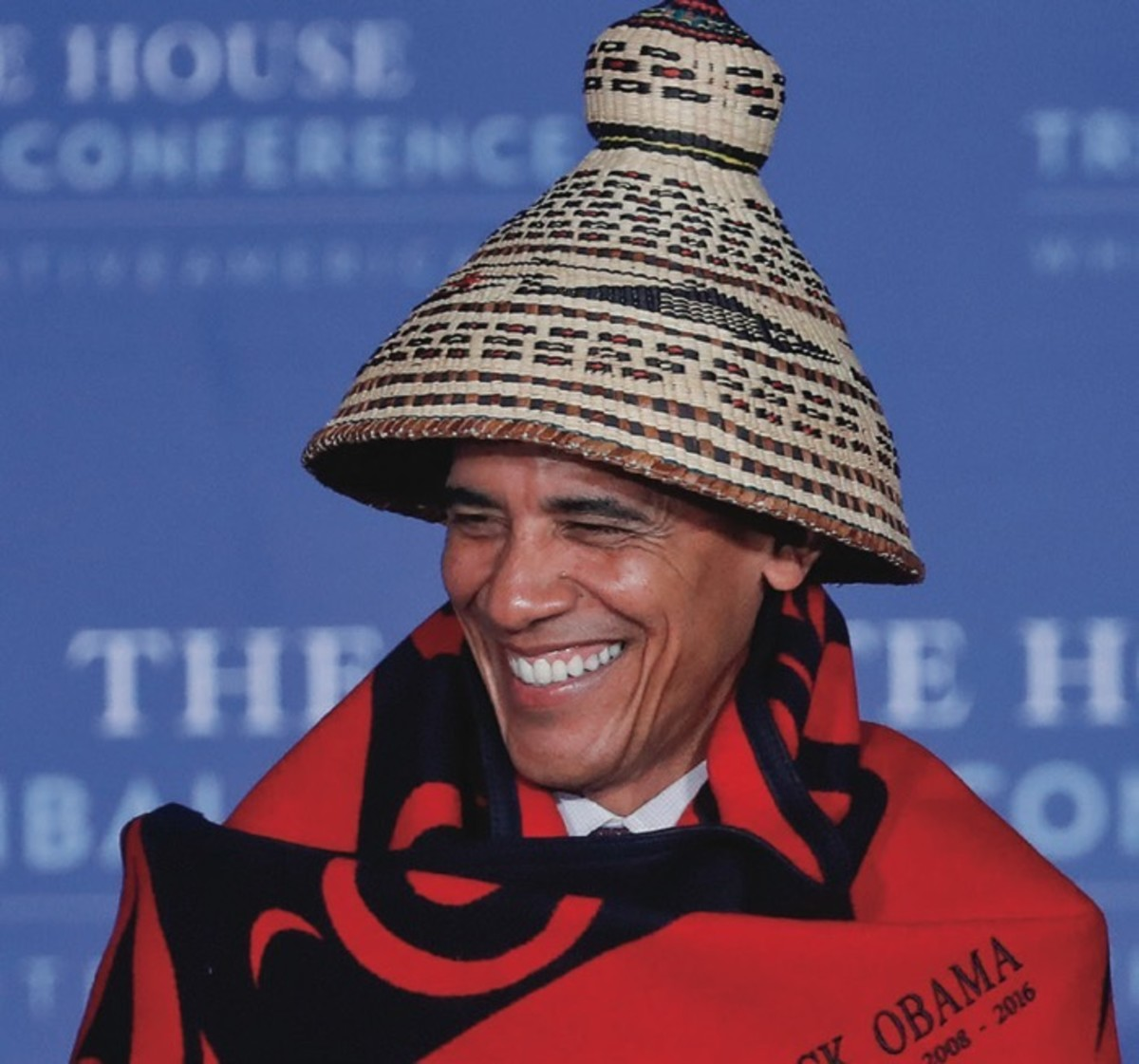 President Barack Obama smiles as he wears a ceremonial blanket and cedar basket twined hat given to him by Brian Cladoosby, President of National Congress of American Indians, at the 2016 White House Tribal Nations Conference, Monday, Sept. 26, 2016, at the Mellon Auditorium in Washington.